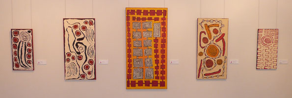 Works by Napurrula, left, and son Morris Gibson, right, flank a large canvas by Patrick Tjungurrayi